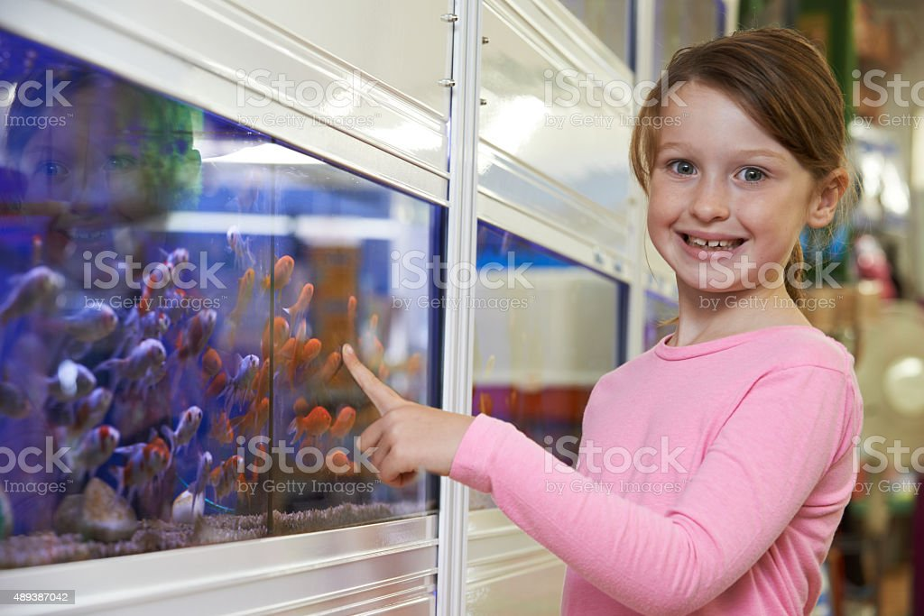 Portrait Of Girl Choosing Goldfish In Pet Shop stock photo