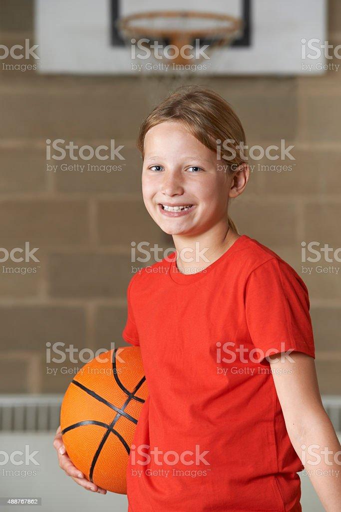 Portrait Of Girl Holding Basketball In School Gym