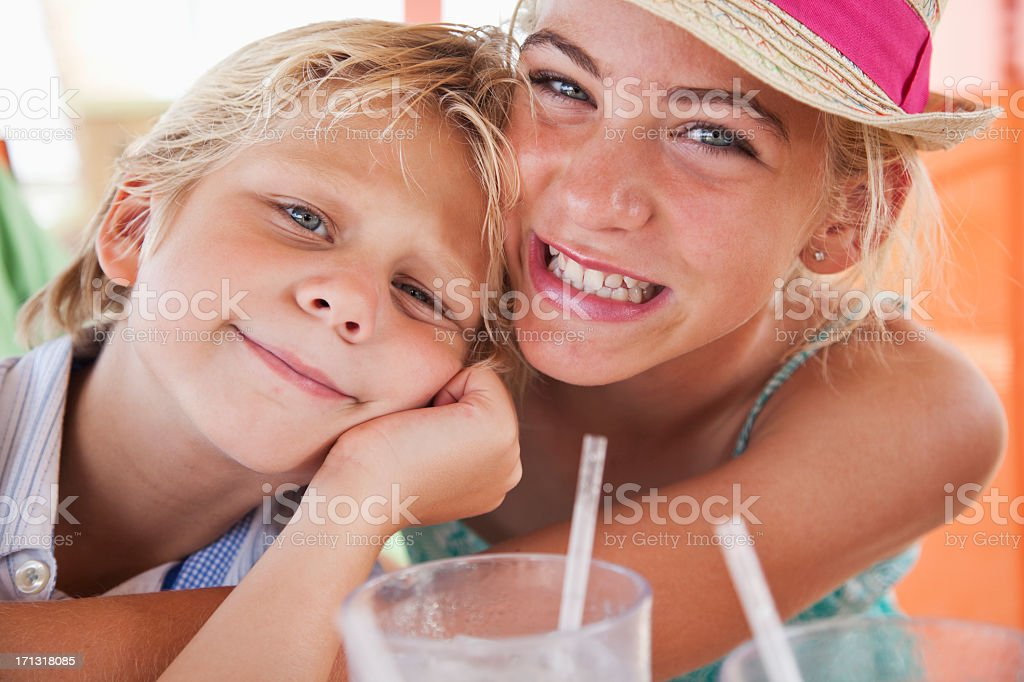 Portrait of girl hugging little brother stock photo