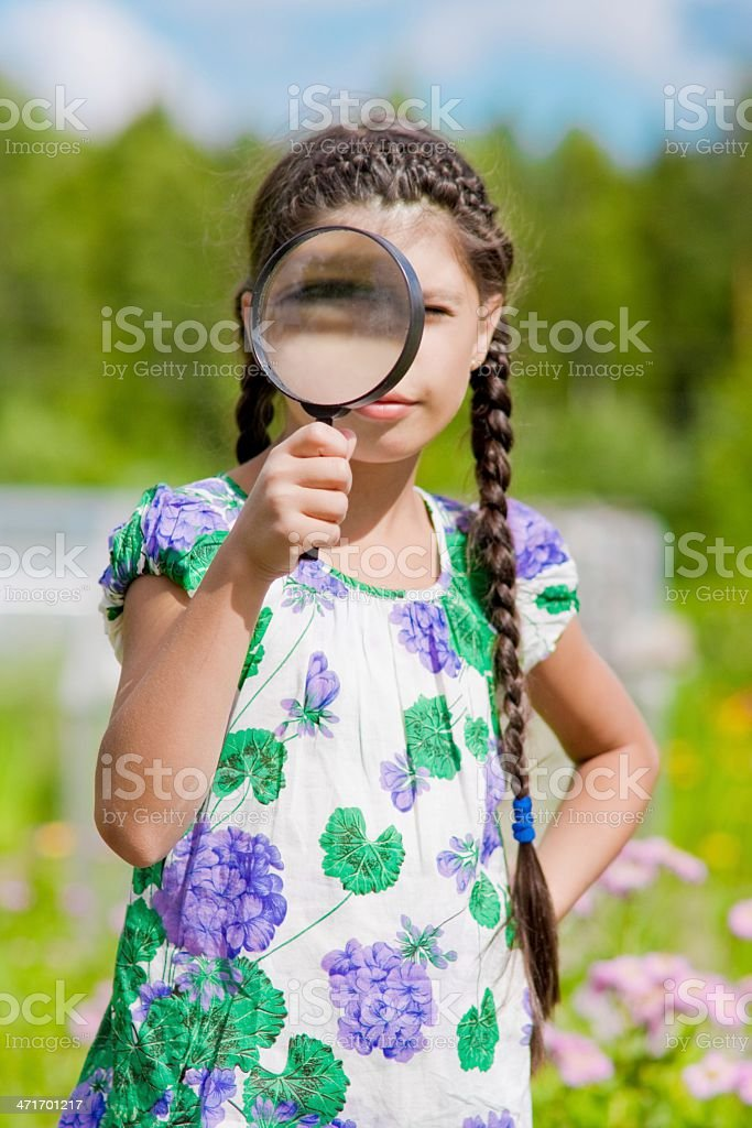 Portrait Of Girl Looking Through Magnifying Glass stock photo