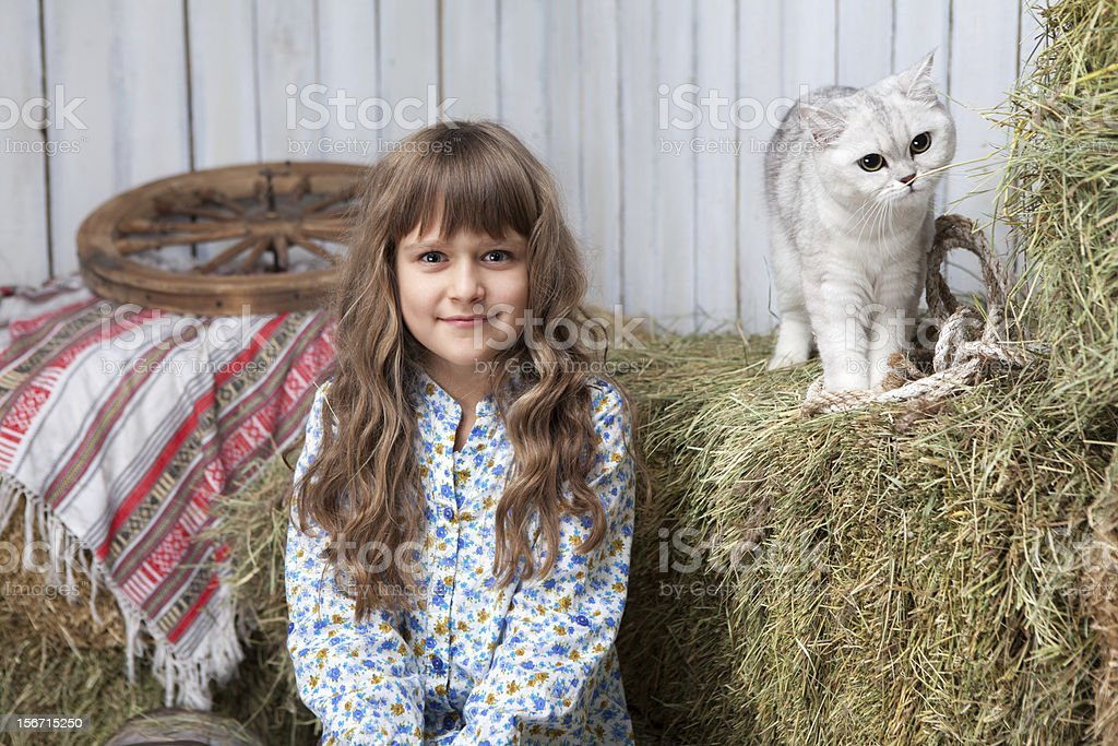 Portrait of girl villager, cat on hay stack in barn royalty-free stock photo
