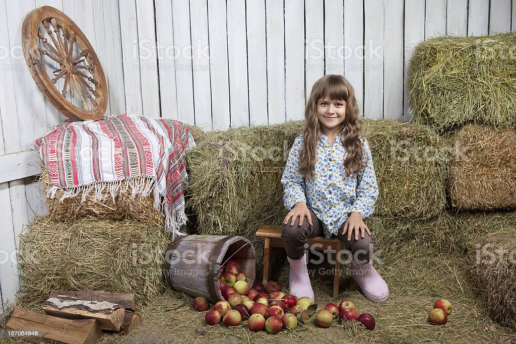 Portrait of girl villager near pail with  apples in hayloft stock photo
