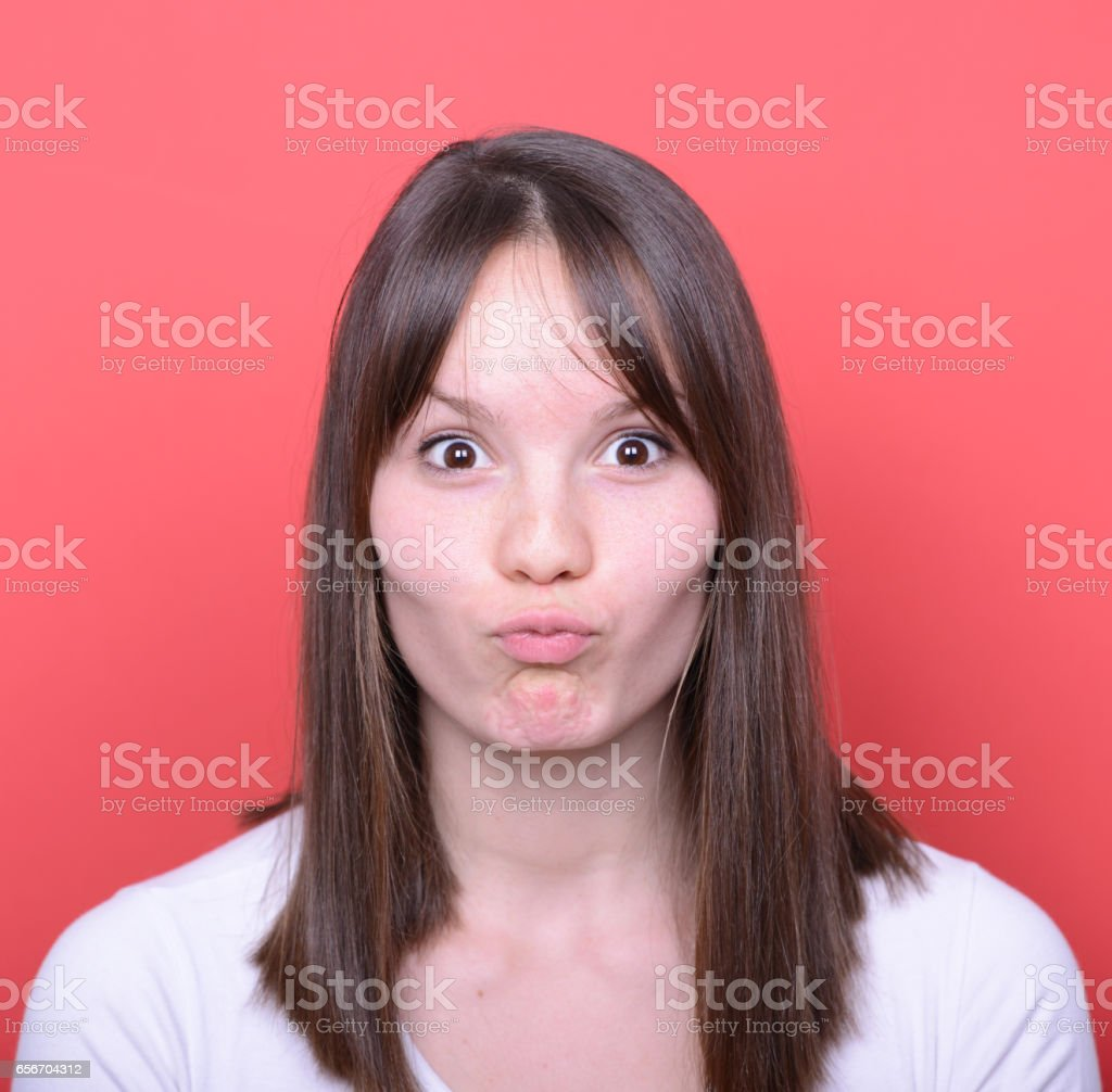 Portrait of girl with funny face against red background stock photo