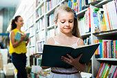 Portrait of glad girl in school age taking book