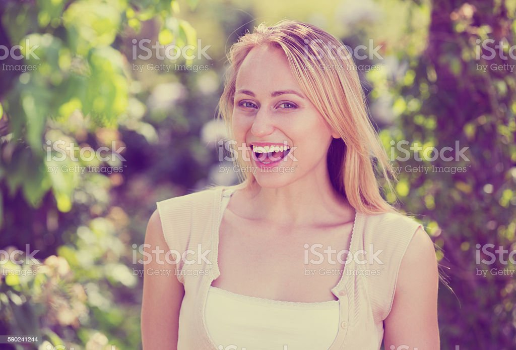 Portrait of glad young blond woman in garden stock photo