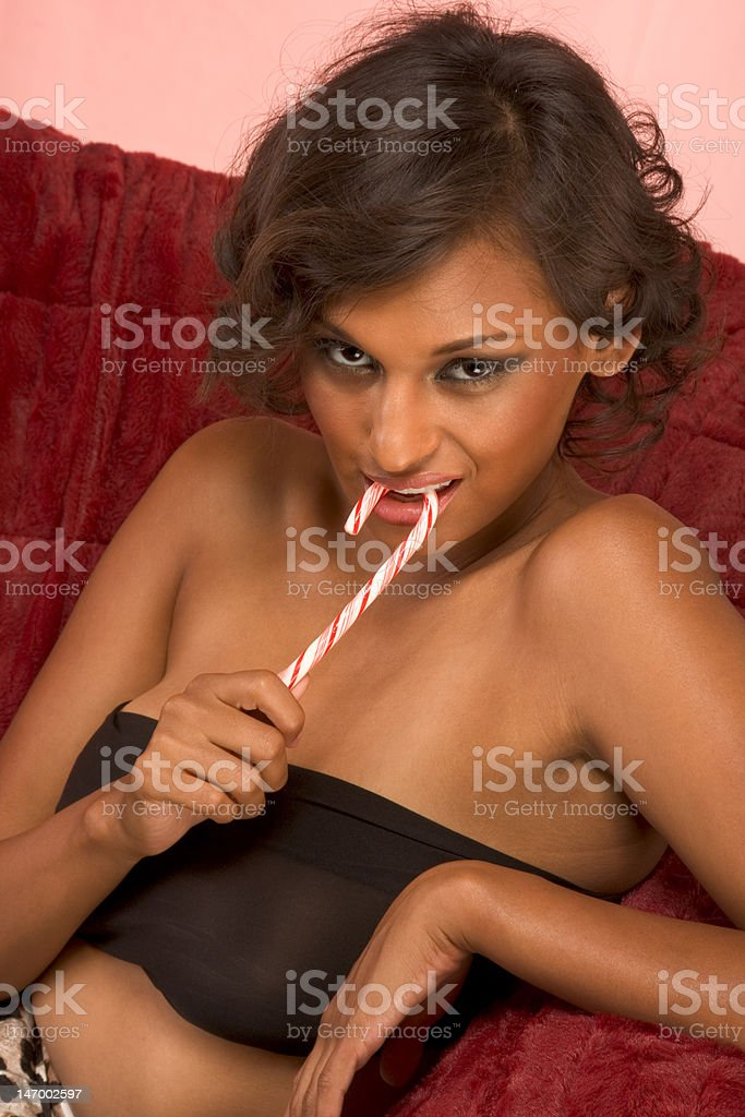 Portrait of glamorous ethnic female with candy cane royalty-free stock photo