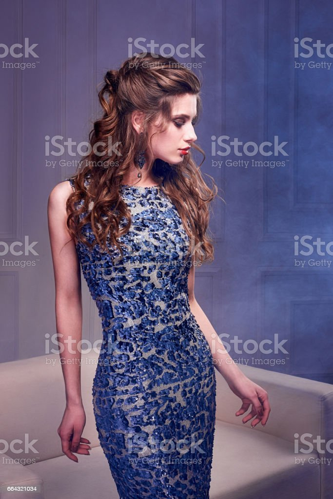 Portrait of gorgeous girl with curly hair long. The beautiful evening cocktail dress. stock photo