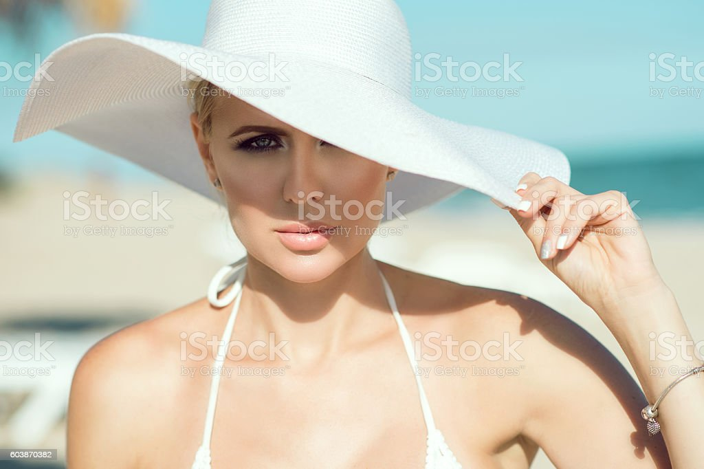 Portrait of gorgeous lady in white bra and wide-brimmed hat stock photo