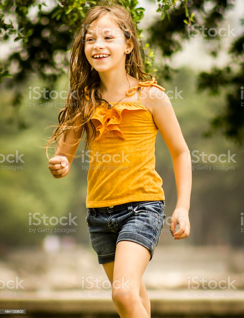 Portrait of Gorgeous Little Girl Playing in Park stock photo