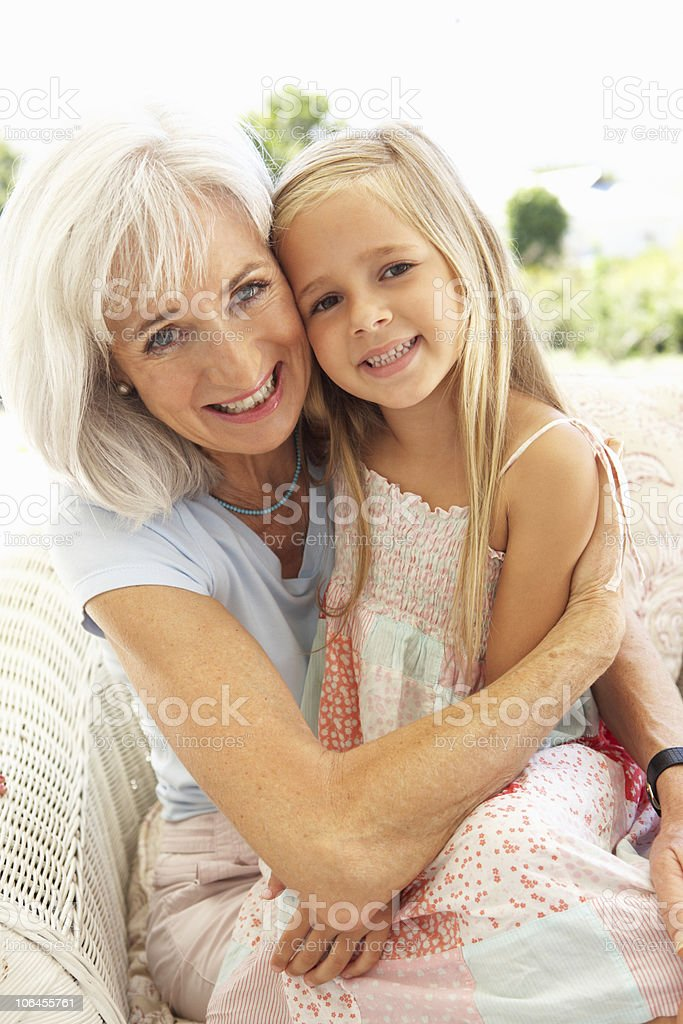 Portrait Of Grandmother With Granddaughter Relaxing On Sofa royalty-free stock photo