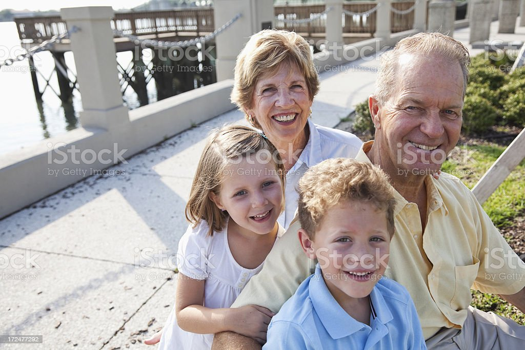 Portrait of grandparents and grandchildren sitting by water stock photo