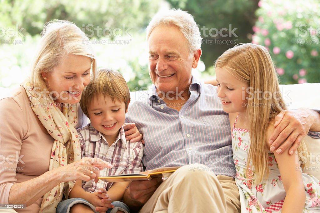 Portrait Of Grandparents Reading To Grandchildren On Sofa stock photo