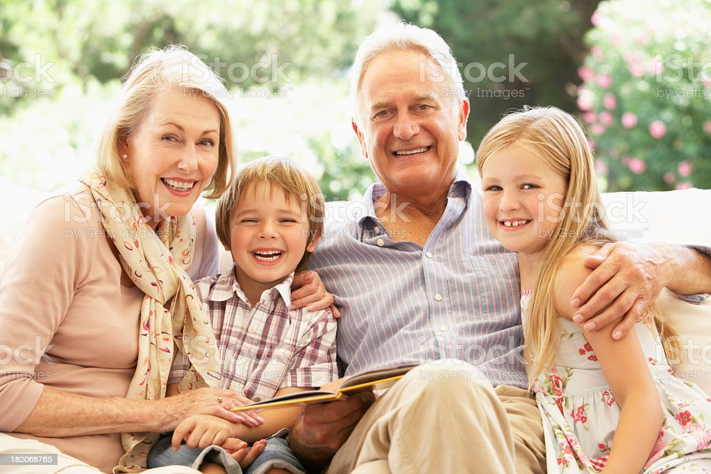 Portrait Of Grandparents Reading To Grandchildren On Sofa royalty-free stock photo