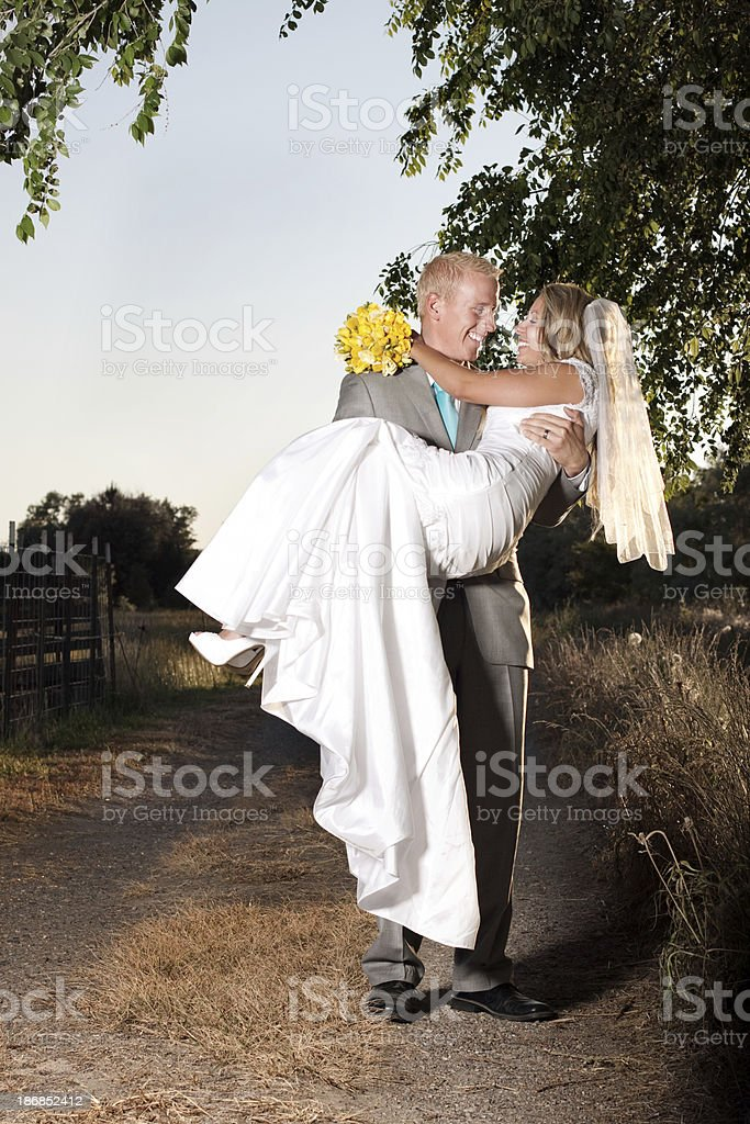 Portrait of Groom Carrying Bride Outdoors with White Sky Background royalty-free stock photo