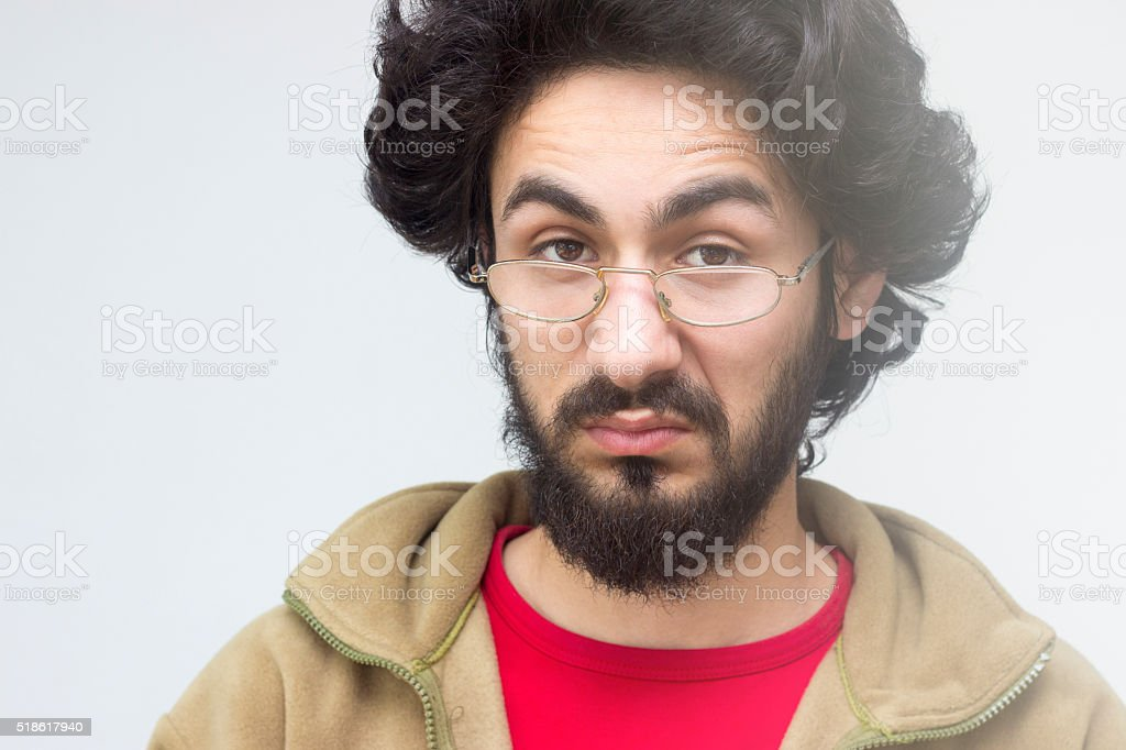 Portrait of grumpy young man over colored background stock photo