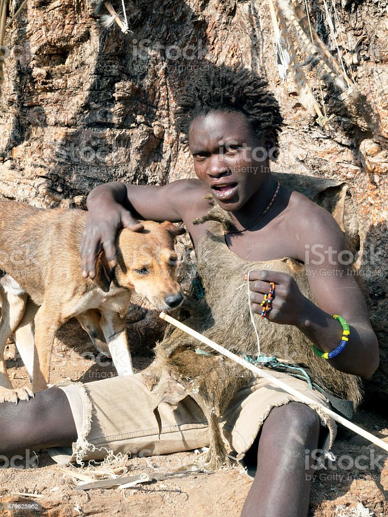 Portrait of Hadzabe young bushman with dogs stock photo