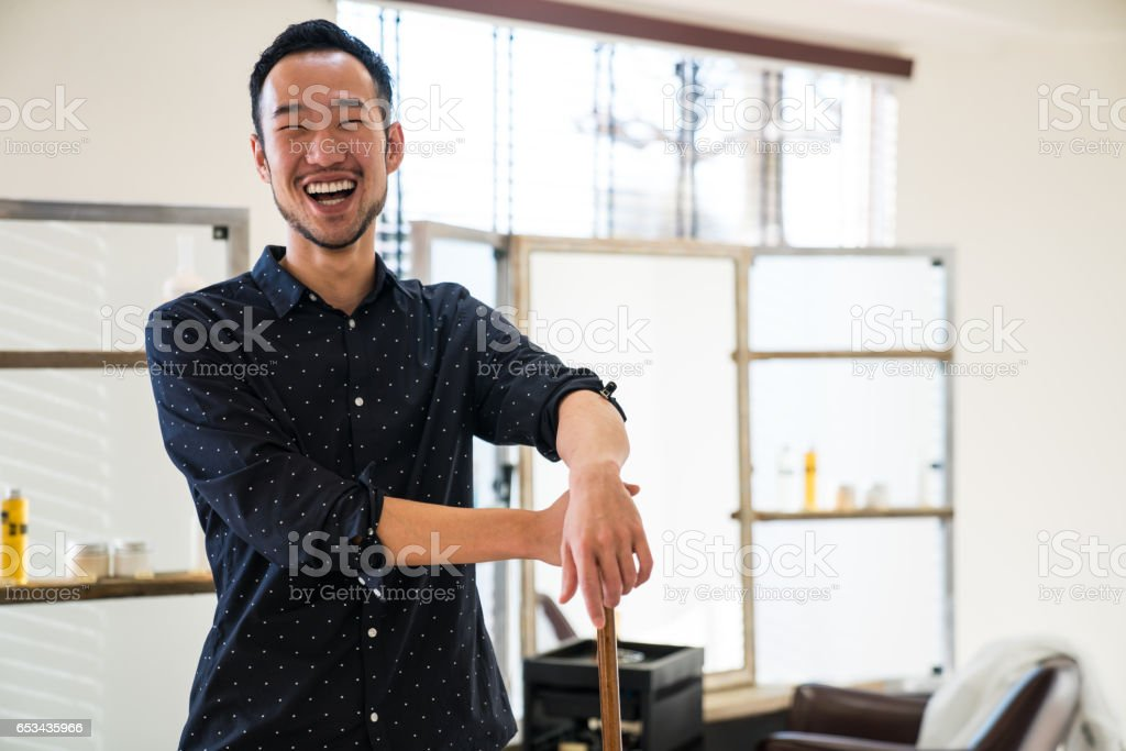 Portrait of hairdresser with broom in his small business salon stock photo