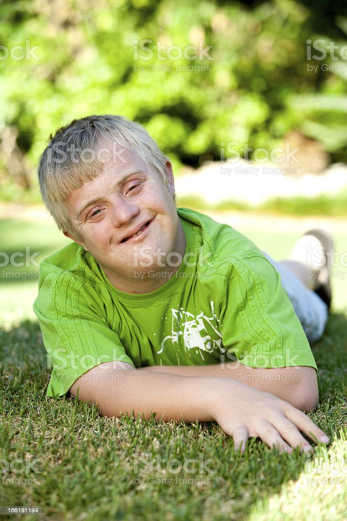 Portrait of handicapped boy on green grass. stock photo