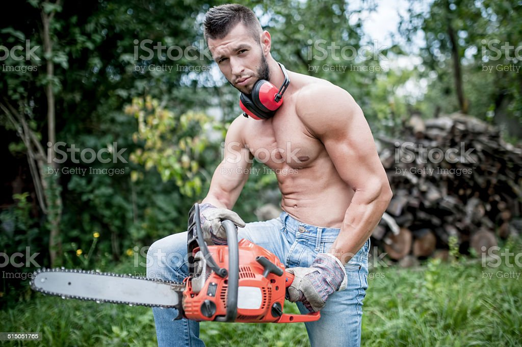 portrait of handsome athletic man with chainsaw and protective gear stock photo