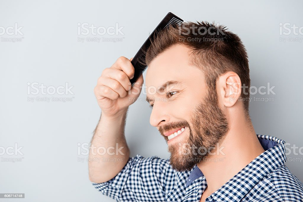 Portrait of handsome cheerful young man combing his hair stock photo