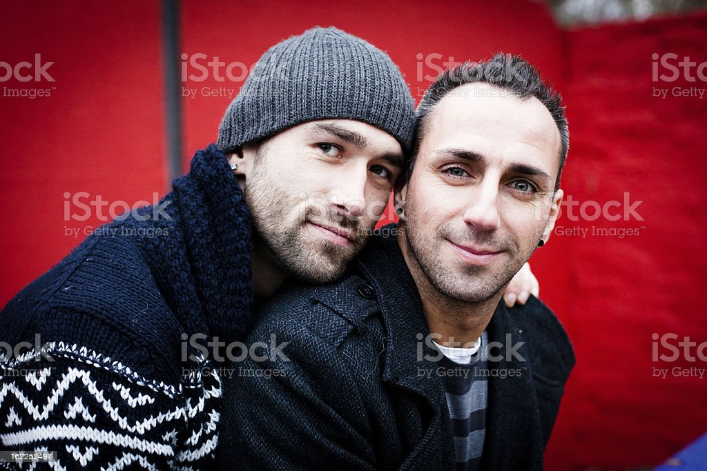 Portrait of handsome homosexual couple in front of red wall stock photo