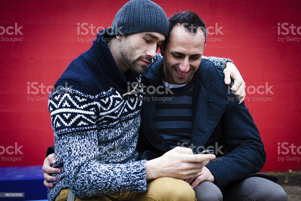 Portrait of handsome homosexual couple in front of red wall royalty-free stock photo