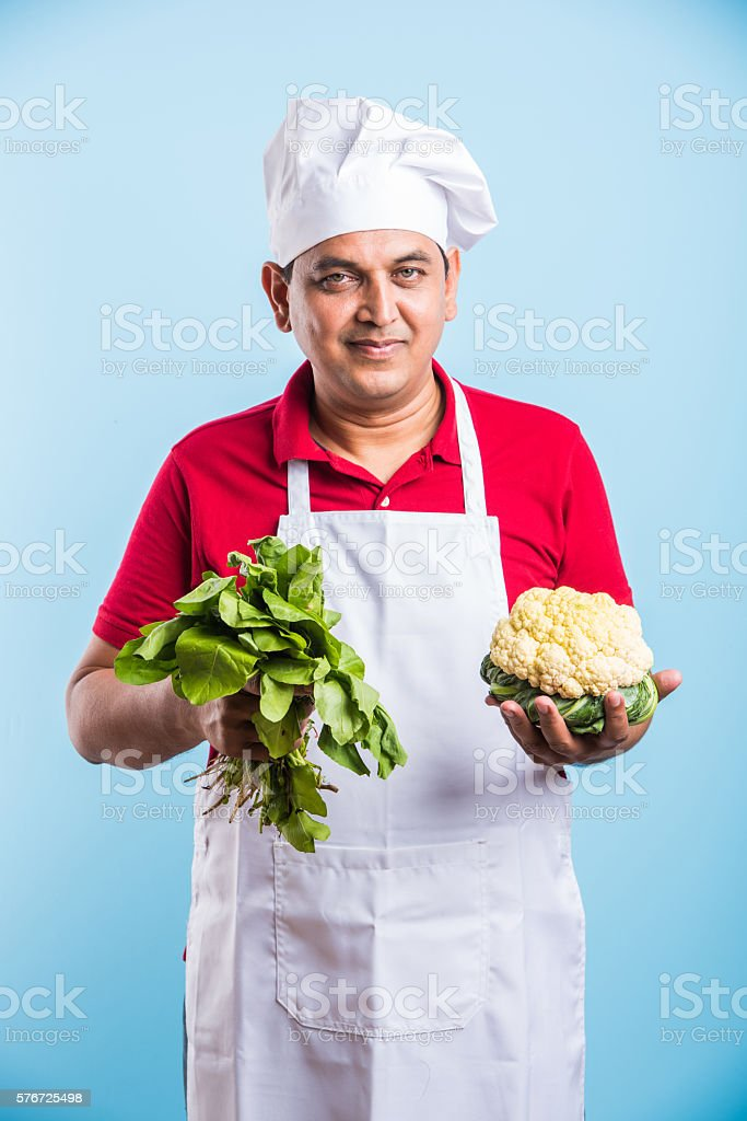 Portrait of handsome Indian male chef with fresh vegetables stock photo