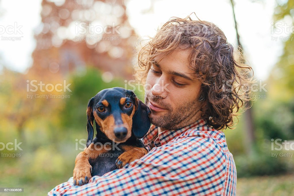 Portrait of handsome man and his dachshund dog in park stock photo