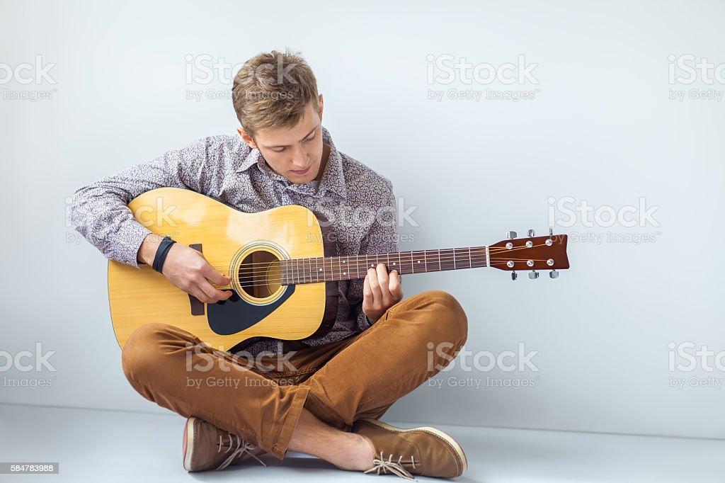 Portrait of handsome man playing guitar siting on floor stock photo