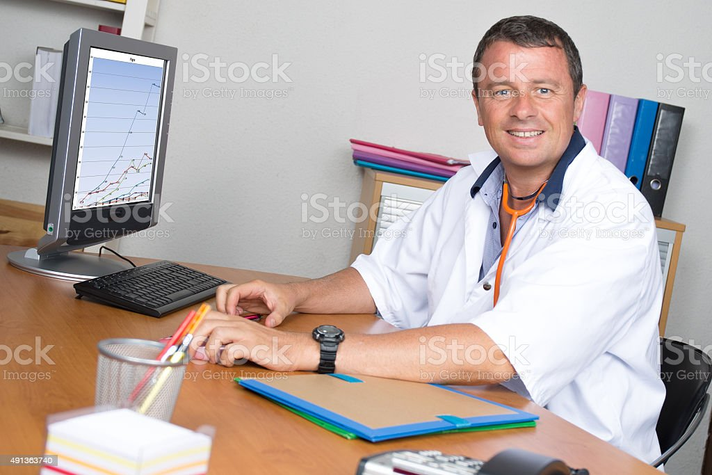 Portrait of handsome mature doctor in office stock photo