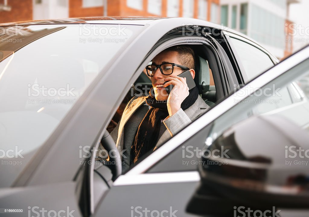 Portrait of handsome modern man driving luxury car in city stock photo