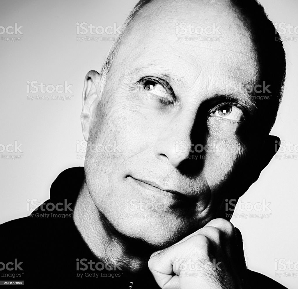 Portrait of handsome older man looking up and to side stock photo
