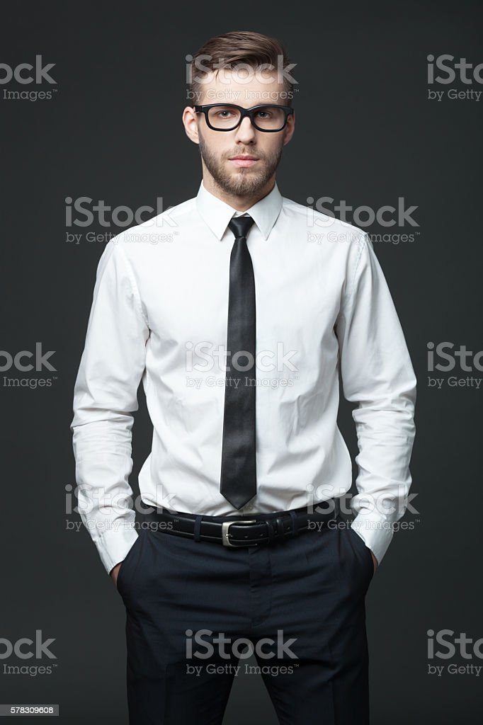 Portrait of handsome young businessman on dark background. stock photo