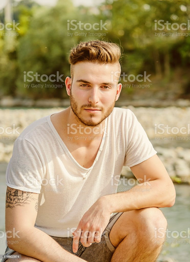 Portrait of handsome young man in white t-shirt outdoors stock photo
