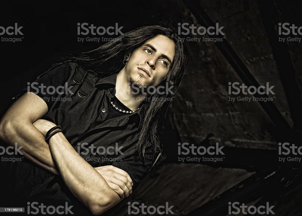 Portrait of handsome young man with long hair. Low key stock photo