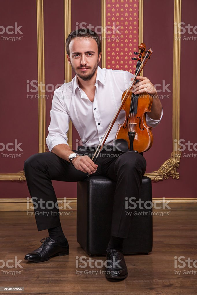 Portrait of handsome young musician playing the violin. stock photo