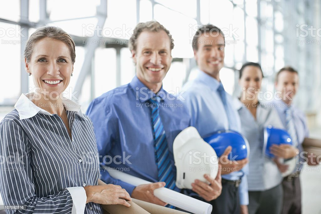 Portrait of happy architects with hardhats and blueprints royalty-free stock photo