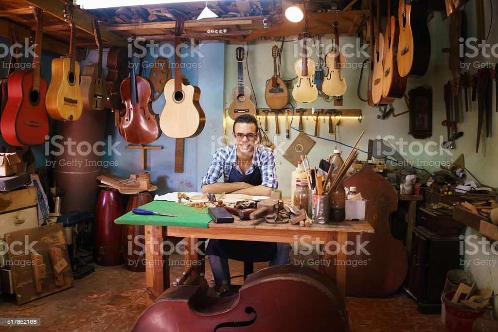 Portrait Of Happy Artisan Lute Maker In Guitar Shop Smiling stock photo