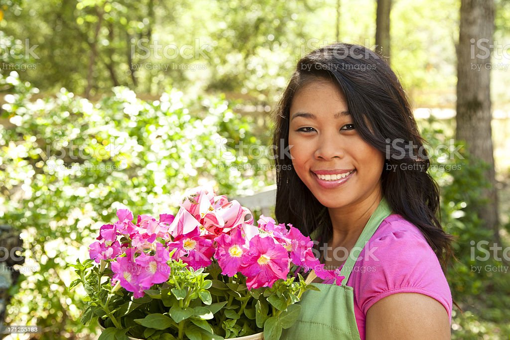 Portrait of happy Asian girl in apron and holding flowers stock photo
