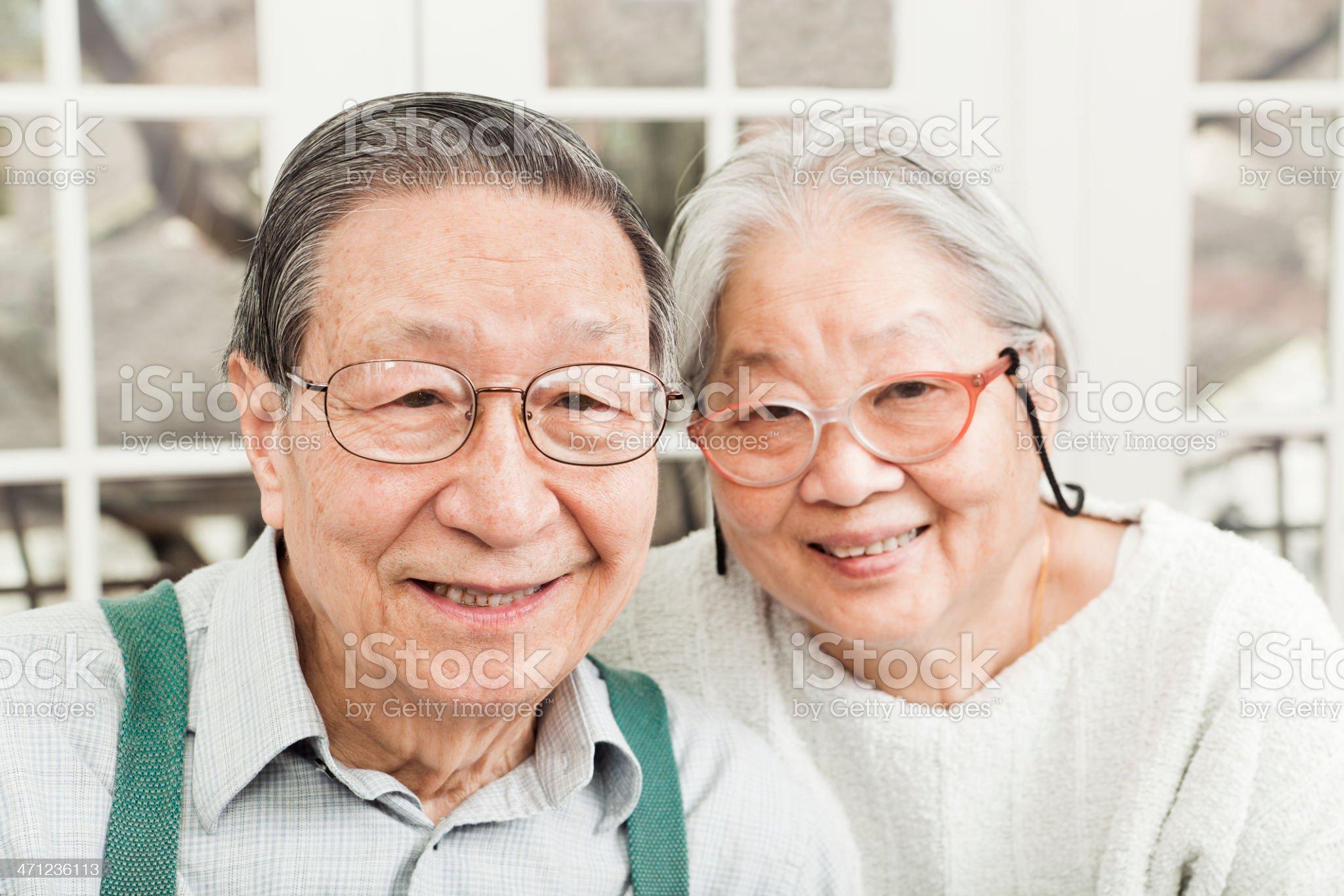 Portrait of Happy Asian Senior Couple by Windows royalty-free stock photo