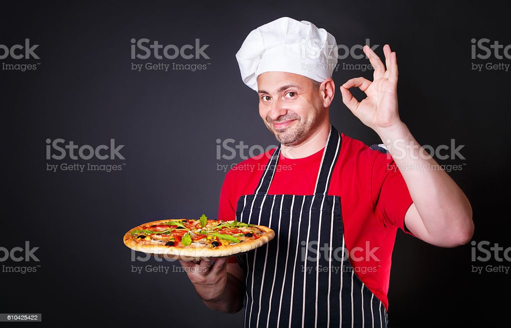 Portrait of happy attractive cook with a pizza in hands stock photo