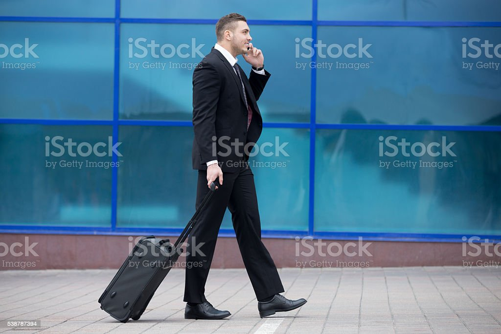 Portrait of happy business man walking with suitcase stock photo
