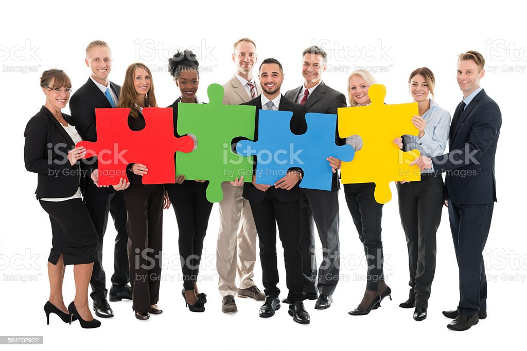 Portrait Of Happy Business Team Holding Jigsaw Pieces stock photo