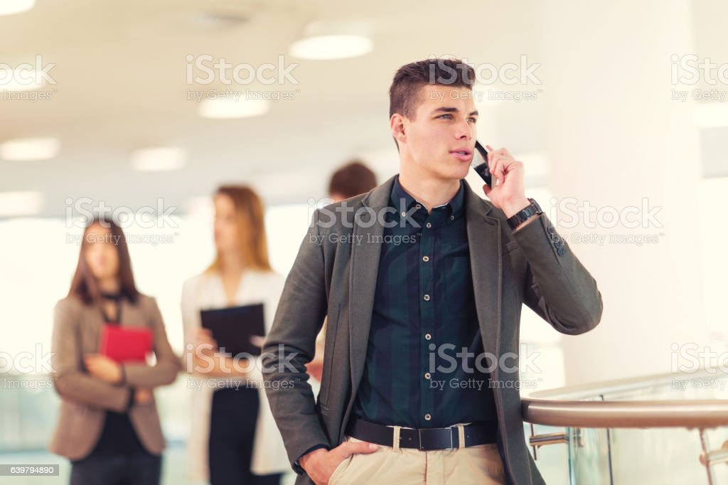 Portrait of happy businessman in office using phone. stock photo