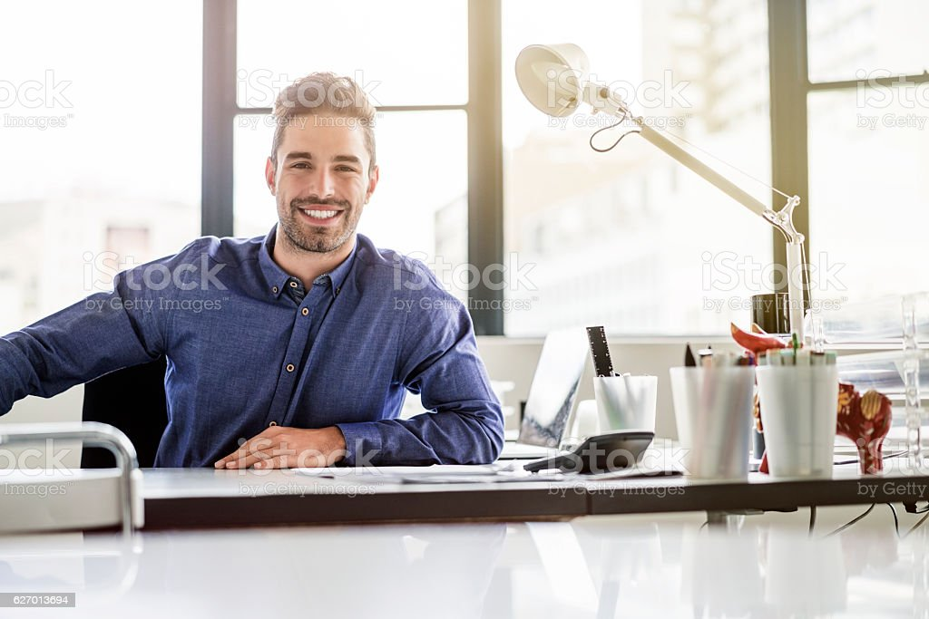 Portrait of happy businessman sitting at desk stock photo