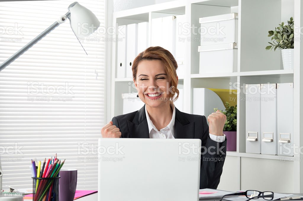 Portrait of happy businesswoman celebrating something with arms stock photo
