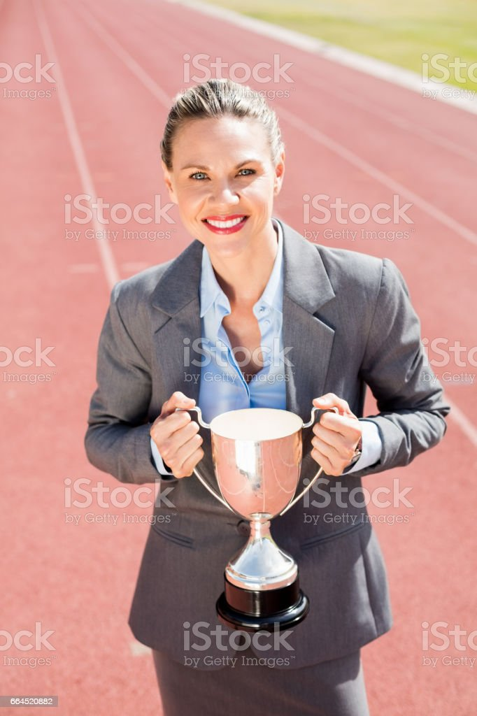 Portrait of happy businesswoman holding a trophy stock photo