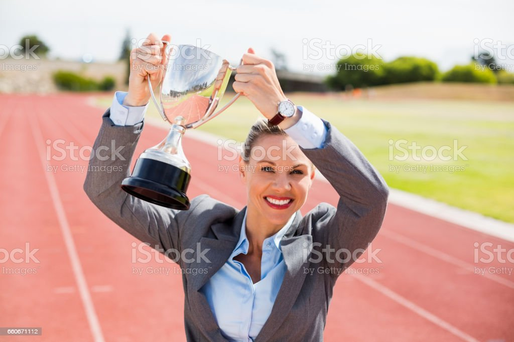 Portrait of happy businesswoman holding up a trophy stock photo