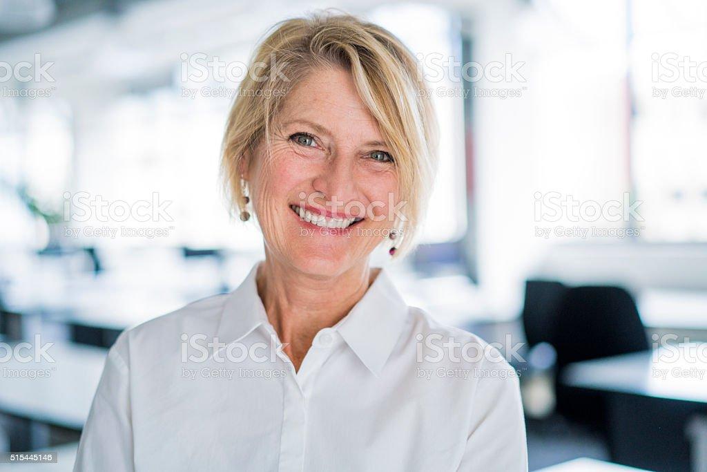 Portrait of happy businesswoman in office stock photo