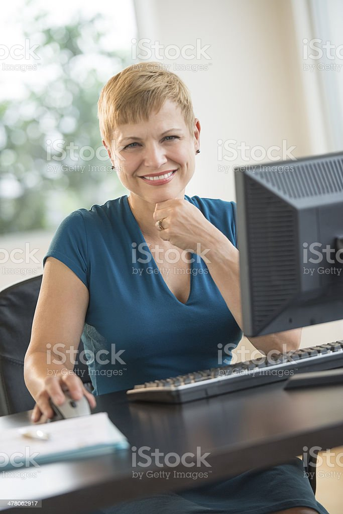 Portrait Of Happy Businesswoman Sitting At Computer Desk royalty-free stock photo